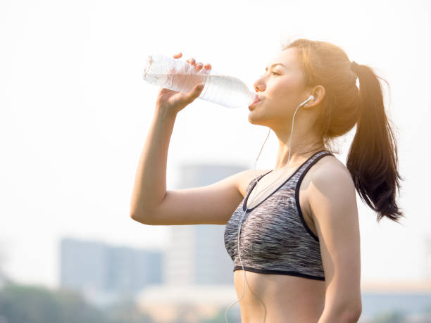 Woman fitness outdoor concept, young asian beautiful woman drinking water during workout, running, jogging, yoga at outdoor park, fresh, relax, happy feeling stock photo
