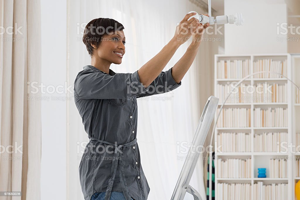 Woman fitting lightbulb stock photo