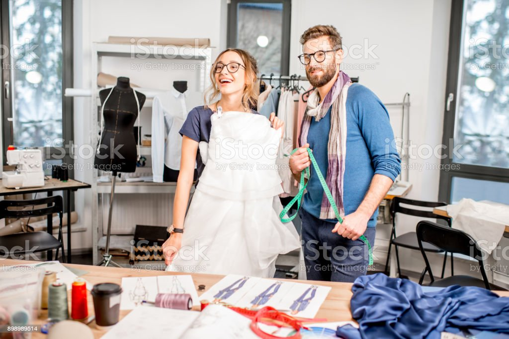 Woman fitting wedding dress at the tailor studio stock photo