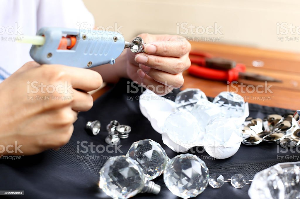 Woman fixing crystal lamps with glue gun stock photo