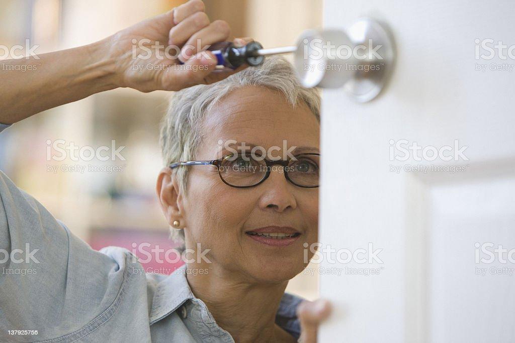Woman fixing doorknob royalty-free stock photo