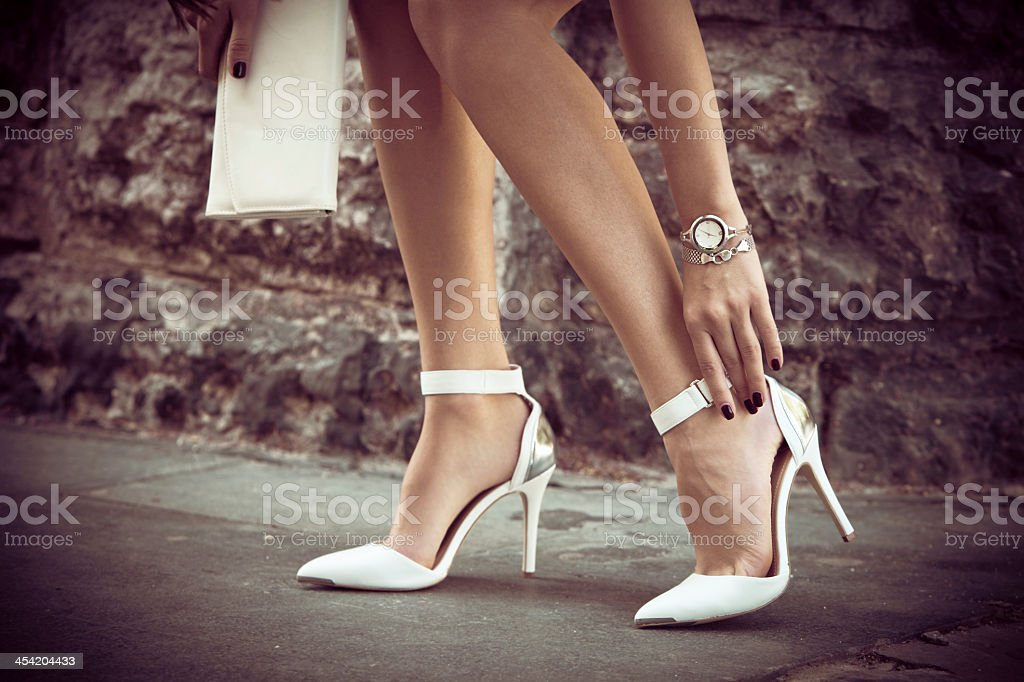 Woman fixing the strap of her elegant high-heeled shoes stock photo