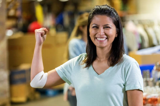 woman flexes muscles after donating blood - blood donation stock pictures, royalty-free photos & images
