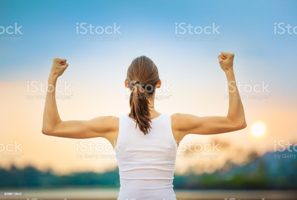 Woman flexing her biceps stock photo