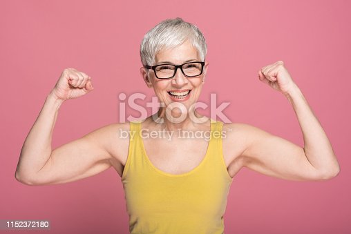Senior fit woman showing her muscles