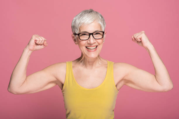 Woman flexing muscles stock photo