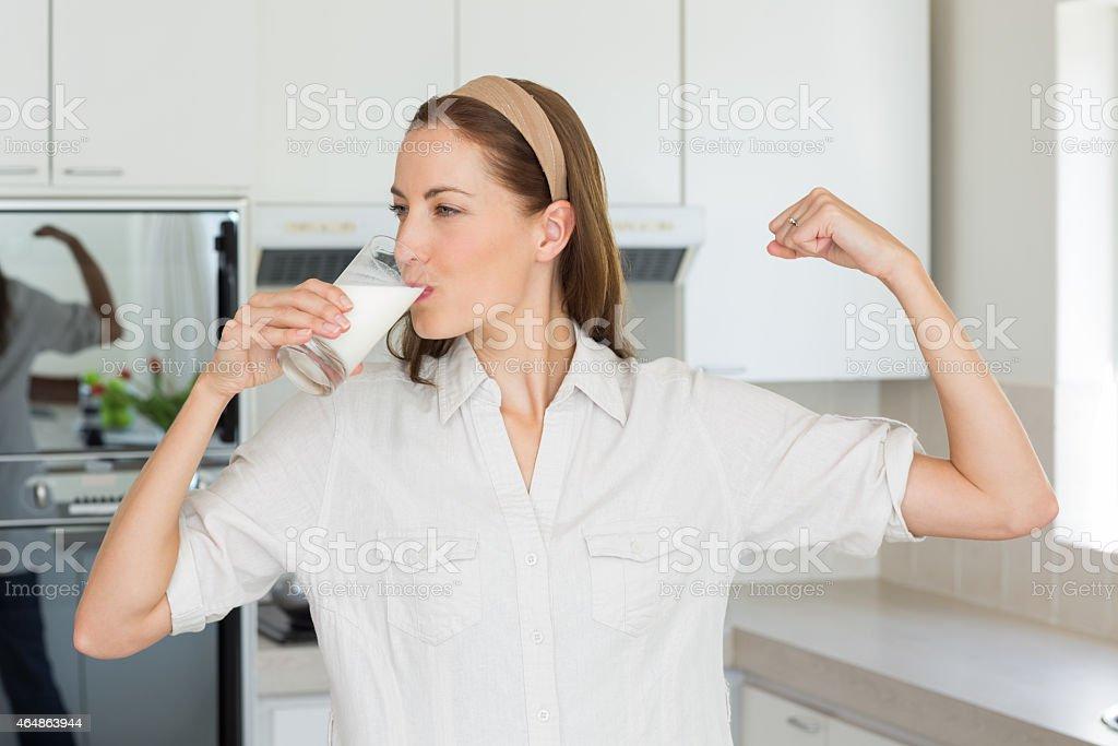 Mujer flexionar los músculos mientras bebe leche en la cocina - foto de stock