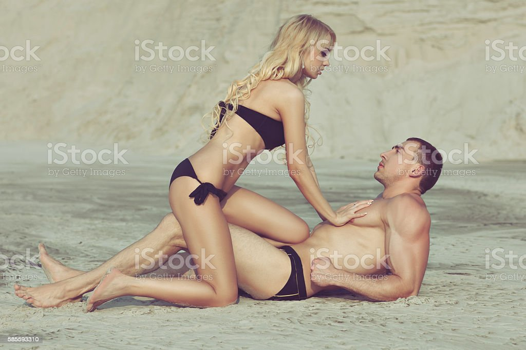 Woman flirting with a man on the beach. stock photo