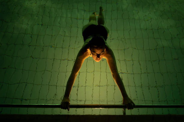 Woman Floating in a Illuminated Swimming Pool at Night stock photo