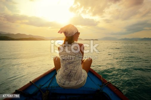 istock Woman floating in boat at sunset 477061785