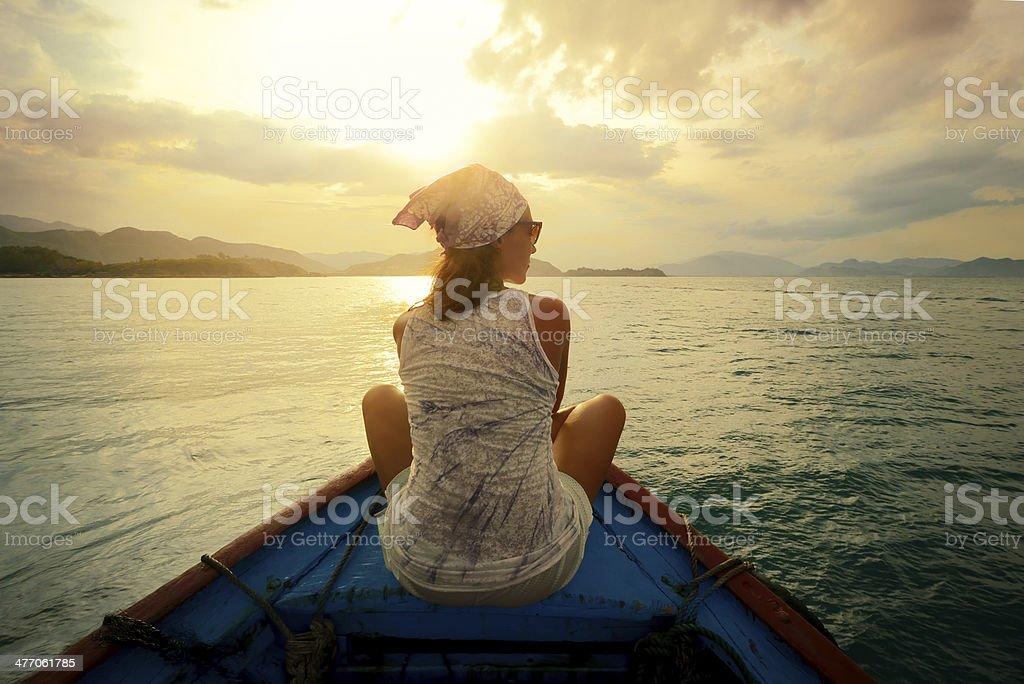 Woman floating in boat at sunset圖像檔
