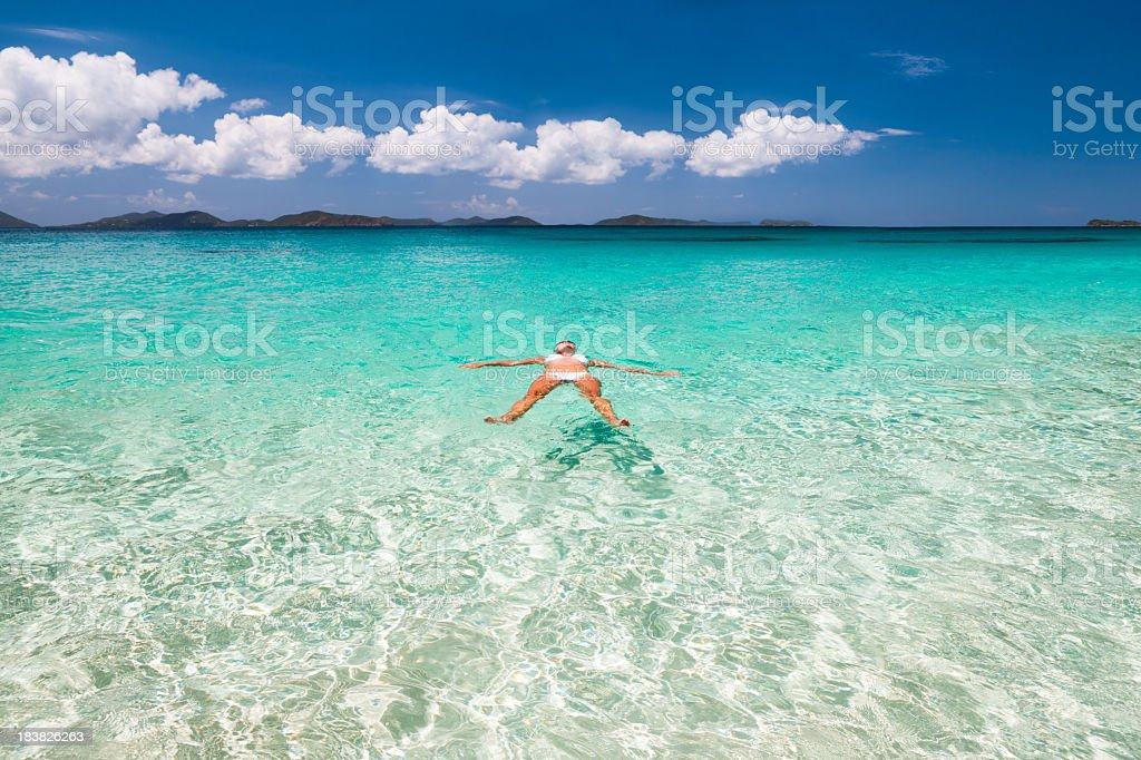 woman floating in crystal clear water at a Caribbean beach stock photo
