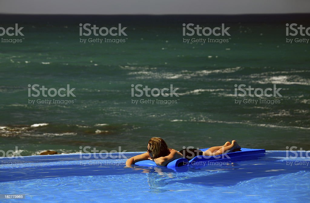 Woman Floating in Infinity Pool royalty-free stock photo