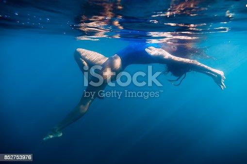 888067280istockphoto Woman floating in sea, underwater in blue ocean 852753976