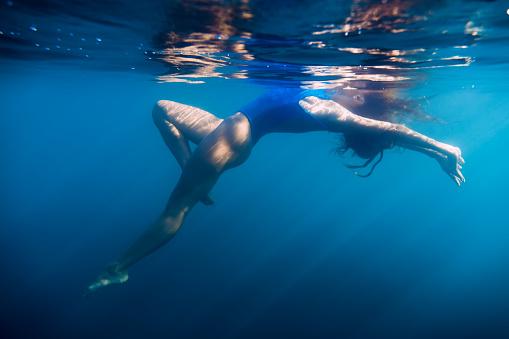 888067280 istock photo Woman floating in sea, underwater in blue ocean 852753976