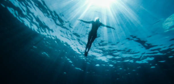 woman floating in the sea and rays of light piercing through - swim arms imagens e fotografias de stock