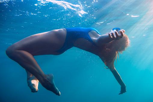 888067280 istock photo Woman floating in underwater, blue ocean. 848298478