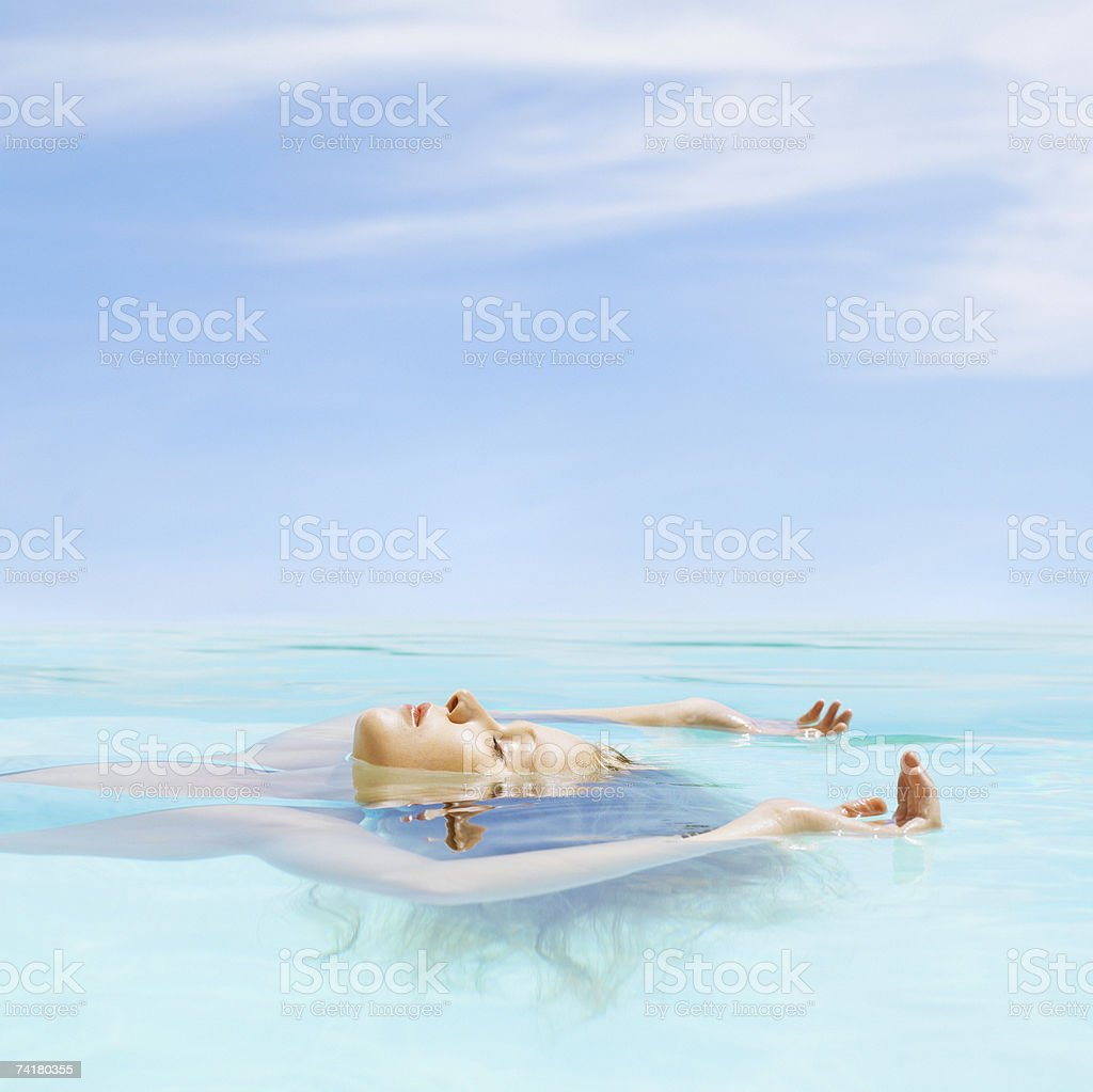 Woman floating in water stock photo