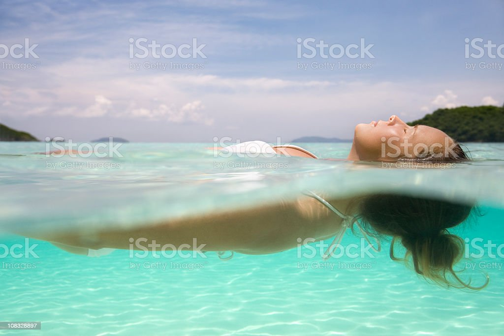woman floating on crystal clear water in the Caribbean stock photo