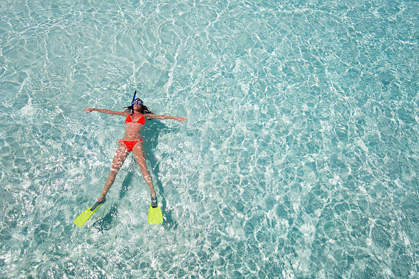 Woman floating on crystal clear waters foto