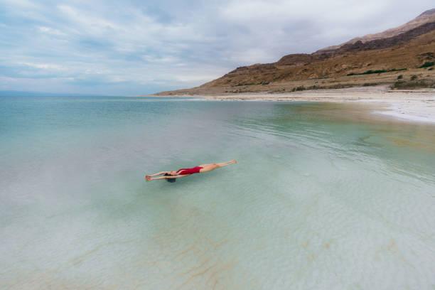 woman floating on water  in dead sea - morze martwe zdjęcia i obrazy z banku zdjęć