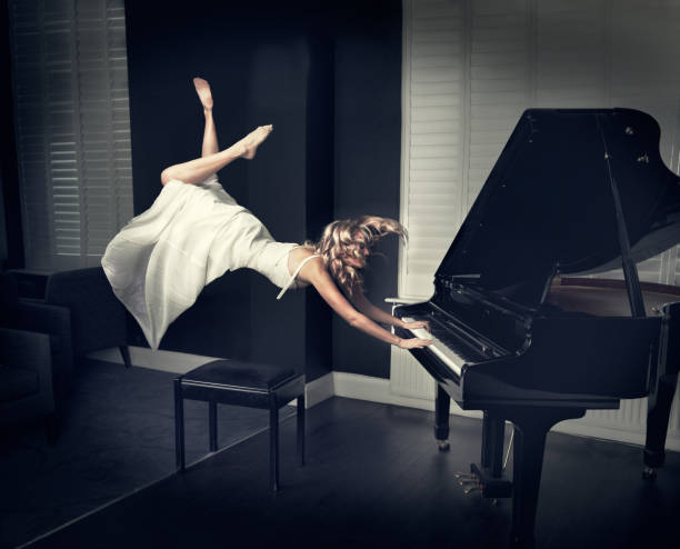 Woman floating while playing piano stock photo
