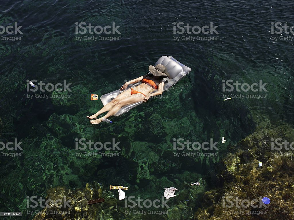 Woman floats in the sea amongst trash royalty free stockfoto