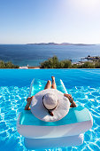 Attractive woman with a white sunhat floats on a swimming pool and enjoys the view to the sea during summer vacation time