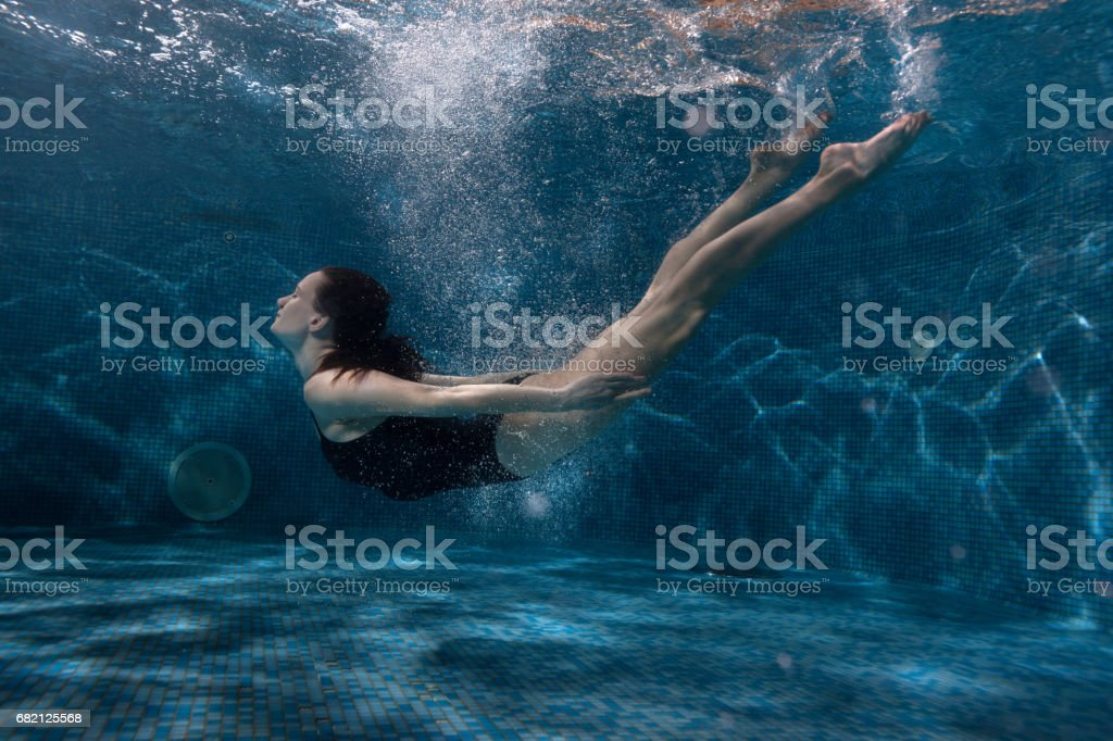 Woman floats under water in the pool. stock photo