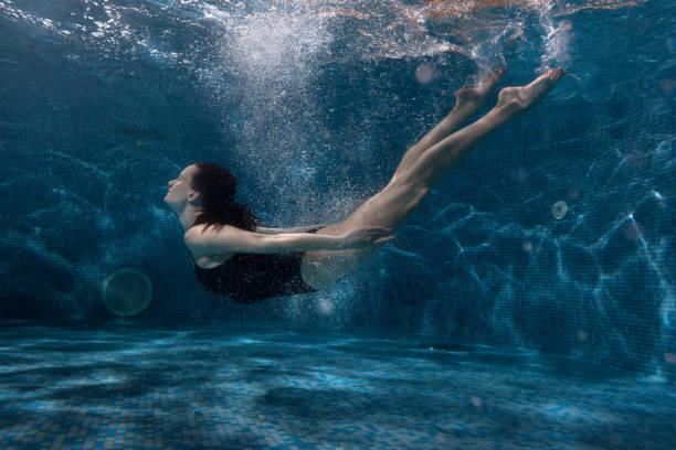 woman floats under water in the pool. - meerjungfrau kleid stock-fotos und bilder