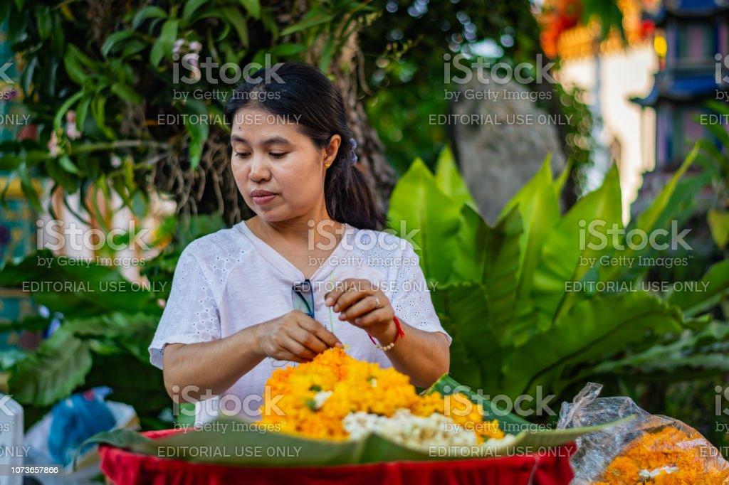 Woman florist arranges orange flowers at the Buddhist temple of Wat Pho in Bangkok, Thailand – zdjęcie