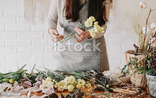 woman florist collects a bouquet decorates from different flowers