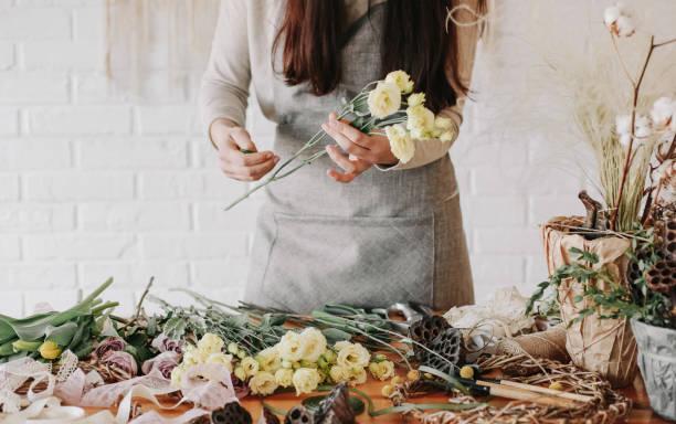 femme fleuriste recueille bouquet décore de fleurs différentes - fleuriste photos et images de collection