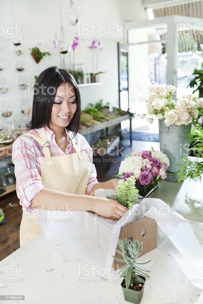 A happy young woman entrepreneur business owner florist in her store...