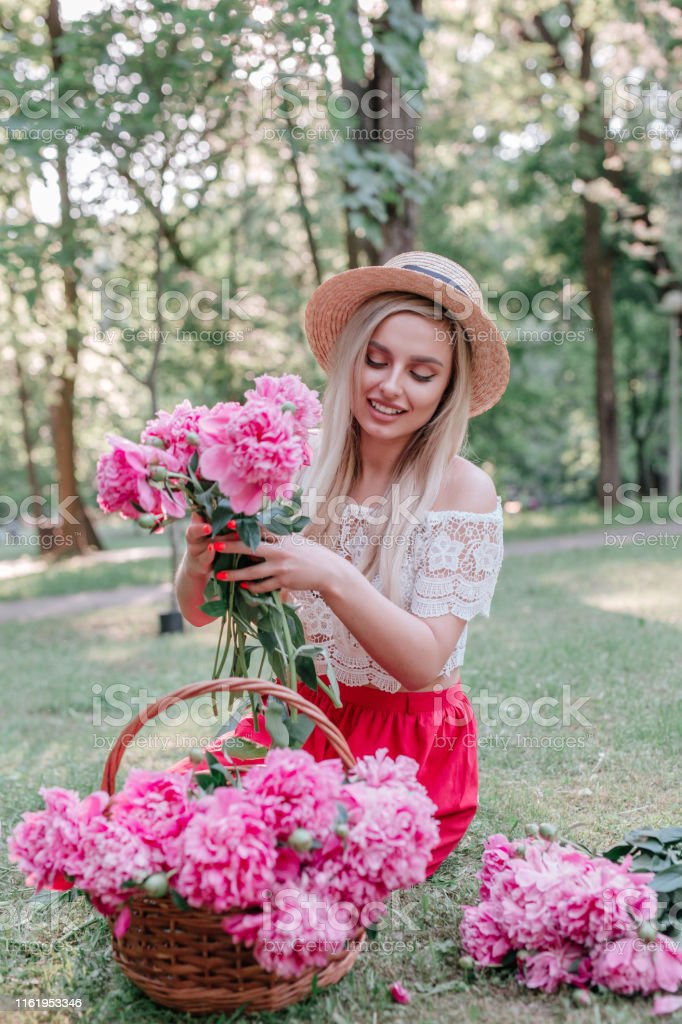 woman florist makes a bouquet with pink peonies flowers outdoor