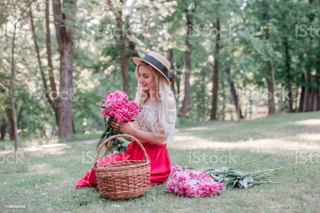 Romantic woman florist in straw hat makes a bouquet with pink peonies...