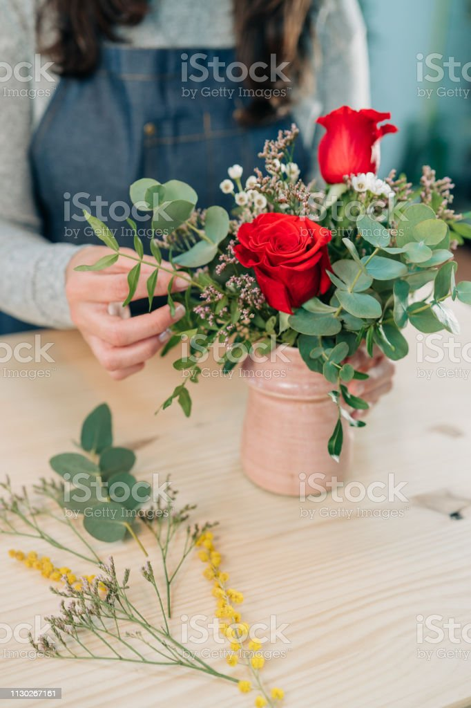 Woman florist makes a red roses bouquet on wooden table
