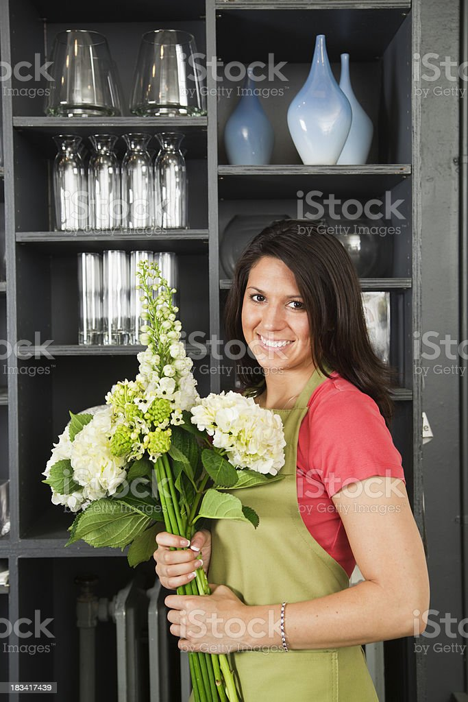 Woman Florist with Bouquet of Flowers by Flower Shop Display royalty-free stock photo