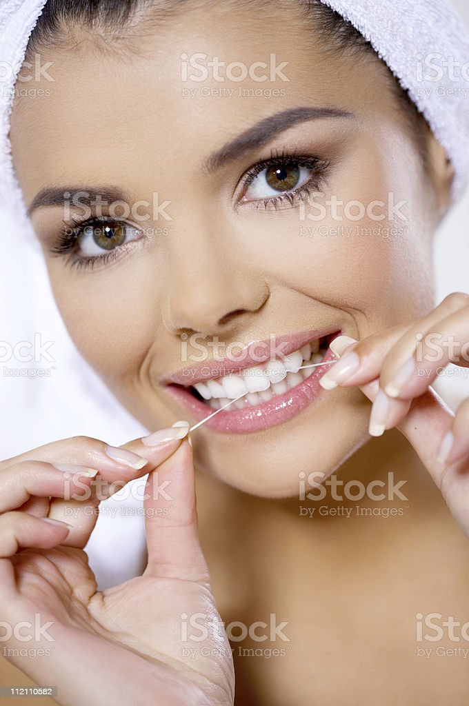 Woman flossing her teeth with towel on head royalty-free stock photo
