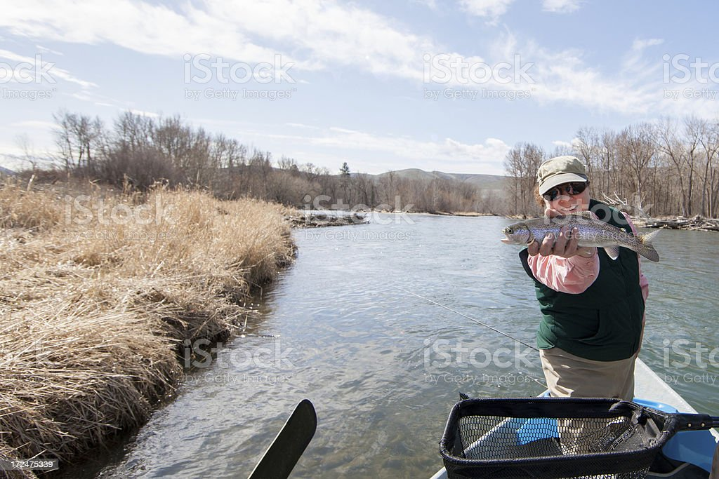 Woman Fly Fishing Holding Trout royalty-free stock photo