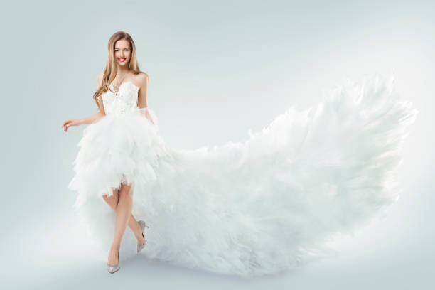 woman flying white dress, elegant fashion model fluttering gown train, studio beauty portrait - prom fashion stock photos and pictures