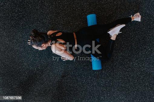 An overhead photo of a woman foam rolling her quadricep muscle after an intense workout.