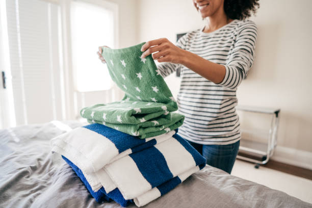 Woman folding towels Woman folding towels arrangement stock pictures, royalty-free photos & images