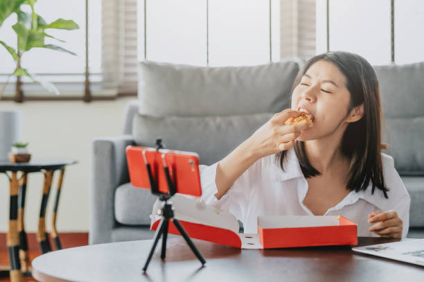 woman food blogger eating pizza while creating new content video stock photo