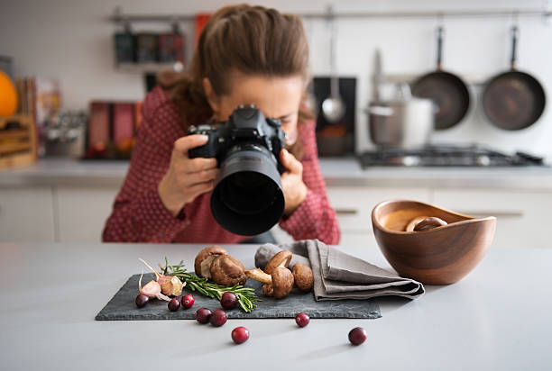 Woman food photographer taking closeup of mushrooms stock photo
