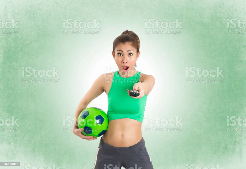 Woman Football Player Holding a Ball and Pointing tv remote on green...