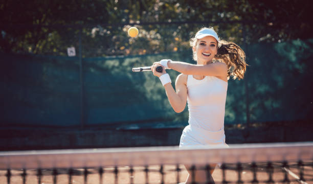 Woman forcefully playing tennis stock photo