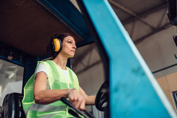 Woman forklift operator driving vehicle Woman forklift operator driving vehicle at industrial factory driver occupation stock pictures, royalty-free photos & images