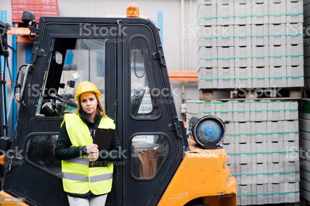 Woman forklift truck driver in an industrial area. stock photo