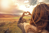 Young woman standing on a hill makes a heart shape finger frame to the spectacular landscape on the background.